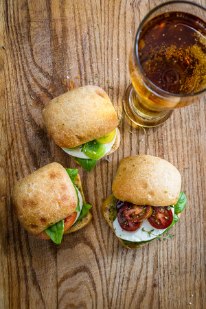 sliders: sliders with fresh mozzarella, tomato and basil served with a refreshing beer