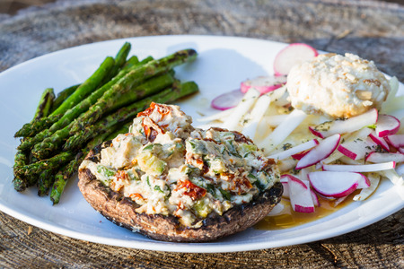 charred: close up of a grilled stuffed mushroom served with charred asparagus and a fennel and radish salad