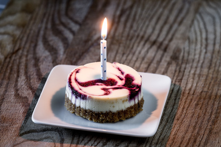 individual serving of huckleberry cheesecake with a birthday candle served on a white plate
