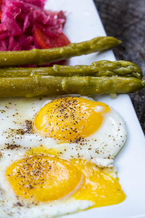 sourced: light breakfast consisting on two fried eggs served with fermented cabbage and asparagus