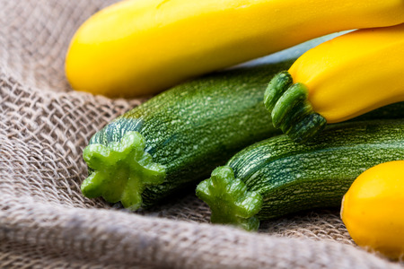 burlap sac: close up of a bunch of fresh picked organic zucchini green and yellow placed on a burlap sac
