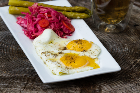 fermented: light breakfast consisting on two fried eggs served with fermented cabbage and asparagus