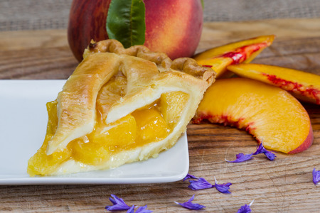 sourced: slice of home made peach pie served on a white plate
