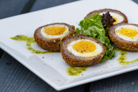scotch eggs served on a whet dish with a green salad in the middle Standard-Bild