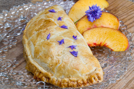 turnover: home made peach turnover served with slices of a fresh peach