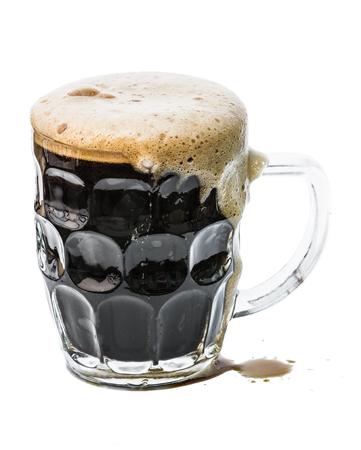 stout: Cerca de una cerveza negra de chocolate se vierte en una taza fría aislada en un fondo blanco