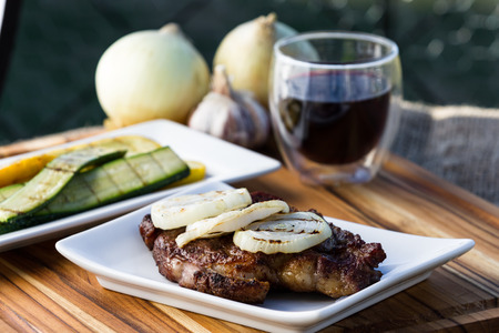 sourced: ribeye steak served with sliced onions and grilled zucchini with a glass of red wine