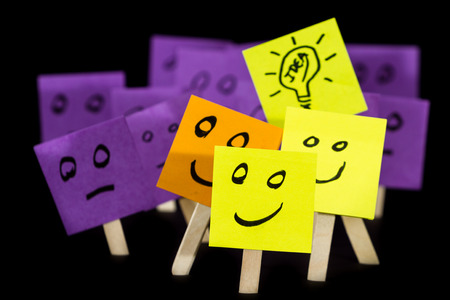 being: conceptual image using sticky notes with hand drawn faces on them isolated on a black background