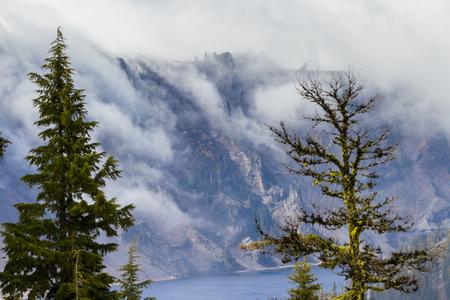 creep: changing temperatures in spring cause a dense fog to creep over the rim and into the crater in Crater Lake Oregon