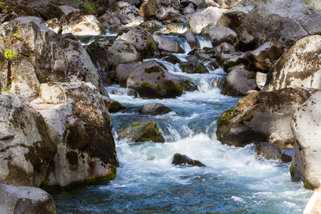 rushing water: tranquil scene with fresh water rushing over and around boulders