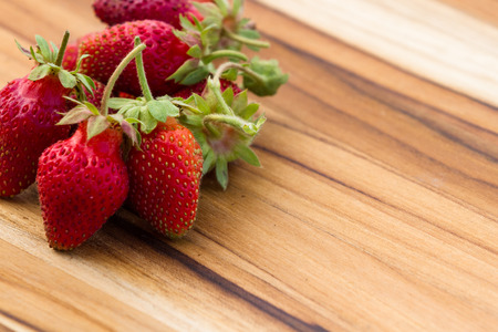 pesticide free: close up of a bunch of freshly picked red wild strawberries on a wooden table Stock Photo