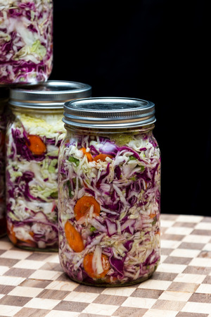 home made cultured or fermented vegetables in a jar over a dark background