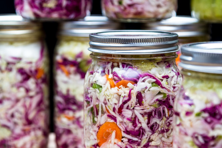 zelfgemaakte gekweekte of gefermenteerde groenten in potten met meer op de achtergrond Stockfoto