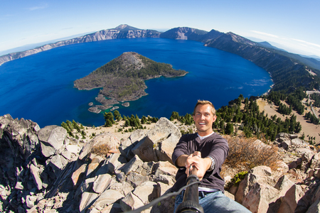 young man taking a self portrait with Crater Lake in the background 版權商用圖片