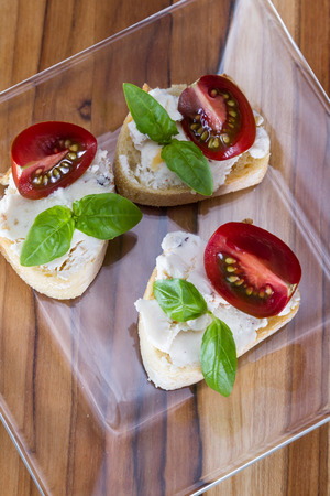 sourced: small bite size appetizer with goat cheese and tomato on a piece of bread garnished with fresh basil