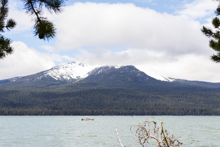 caped: fishing boat in a choppy lake with Diamond peak capped with snow and clouds over it Stock Photo