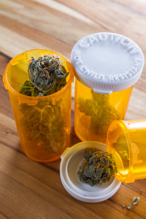 close up of cannabis buds with orange prescription bottles on a wooden table