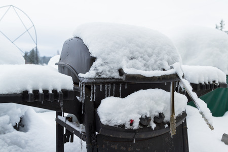 close up of a bar b que grill covered in snow