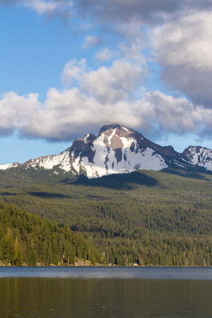 view of mount Thielsen in Oregon with clouds and fog surrounding the peak