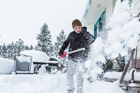 young boy shoveling snow out of the front entrance to his house
