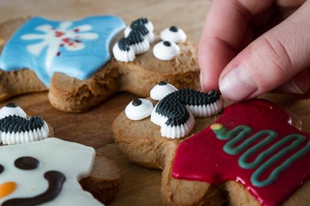 by placing: close up of funny gingerbread cookies on a wooden table with young hands placing decorations and expressions on them