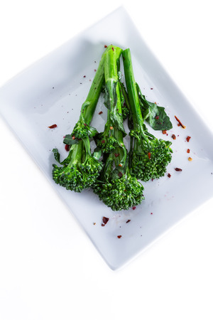 pepper flakes: organic broccoli saut�ed and seasoned with olive oil and red pepper flakes and sea salt served on a white plate Stock Photo