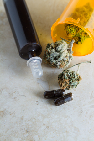 ingestion: close up of an oil made from the essential oil of the cannabis hemp plant with buds next and around the syringe