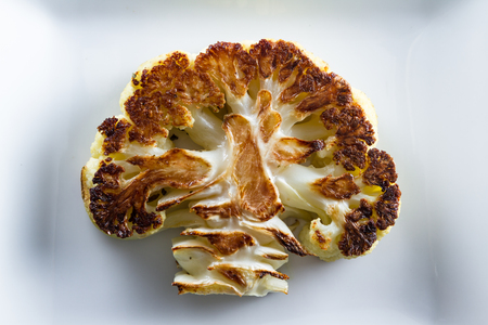 head of cauliflower: sliced roasted head of cauliflower served on a white plate Stock Photo
