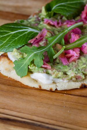 prebiotic: close up of a toasted slice of flat bread topped with a home made spread using avocado and fermented cabbage and then topped with fresh greens.