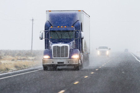 flurry: snowy afternoon on a busy highway with traffic and low visibility for a winter caution concept Stock Photo