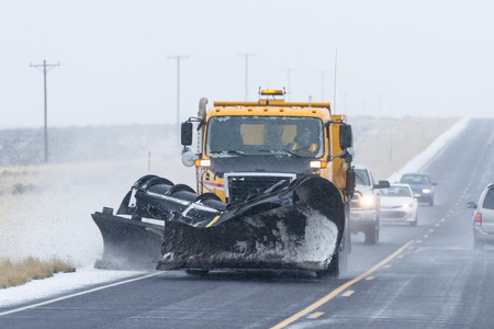 driving conditions: snowy afternoon on a busy highway with traffic and low visibility for a winter caution concept Stock Photo