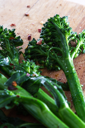 pepper flakes: fresh steamed broccolini seasoned with sea salt and pepper flakes served on a wooden table