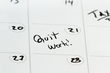 dry erase: the words quit work hand written on a dry erase calendar as a concept