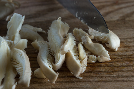 sourced: close up of a chefs hands slicing raw mushrooms on a wooden cutting board