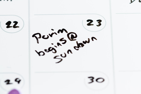 begins: concept using a calendar on march 23 and the words Purim begins at sundown hand written on it