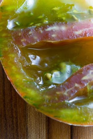 flavorful: beautiful flavorful tomato cut in half  with a colorful pattern and slimy texture
