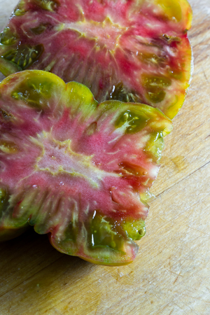 slimy: beautiful flavorful tomato cut in half  with a colorful pattern and slimy texture