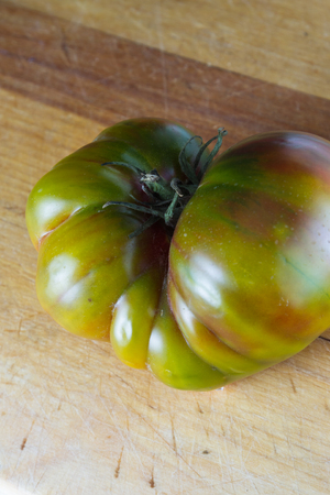the greenish: close up of a greenish heirloom tomato on a wooden cutting board