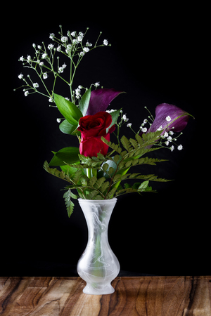 better days: close up of a beautiful flower arrangement over a black background with a beautiful red rose Stock Photo