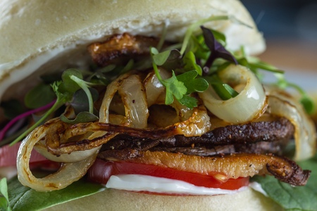 sourced: close up of a fired onion and mushroom sandwich on a gluten free bun with a variety of greens Stock Photo