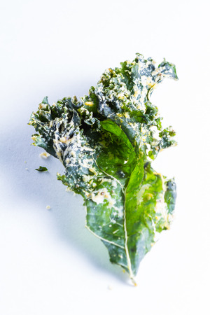 detoxing: close up of a kale chip covered with melted parmesan cheese and spices on a white background Stock Photo
