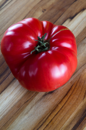 close up of a red heirloom tomato on a wooden cutting board