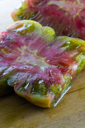 beautiful flavorful tomato cut in half  with a colorful pattern and slimy texture