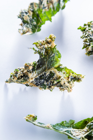 sourced: close up of a kale chip covered with melted parmesan cheese and spices on a white background Stock Photo