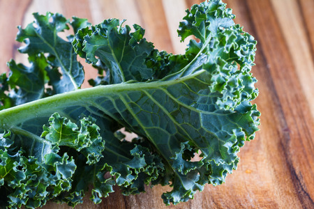 sourced: close up of a leaf of fresh organic kale on a cutting board