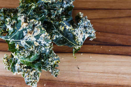 close up of a kale chip covered with melted parmesan cheese and spices