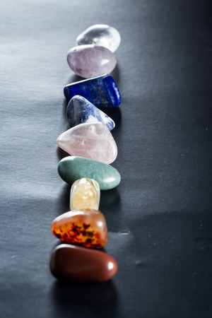 representations: chakra stones lined up on a dark background