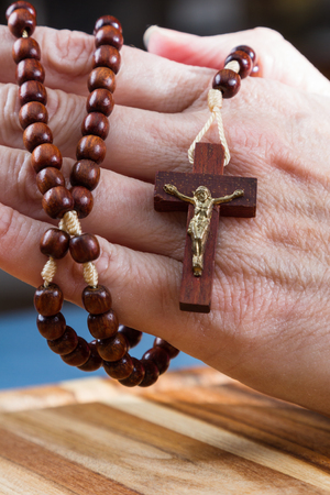 close up of a womans hands holding rosary beads focused on the cross Stock Photo