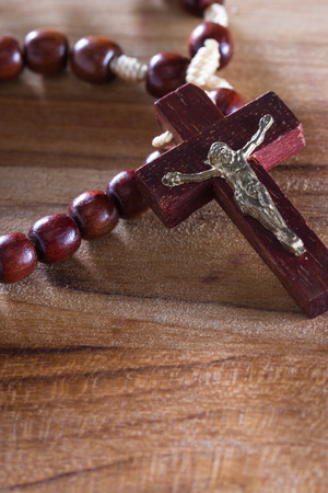 jesus birthday: close up of an old set of rosary beads with a hand made wooden cross as a religious symbol
