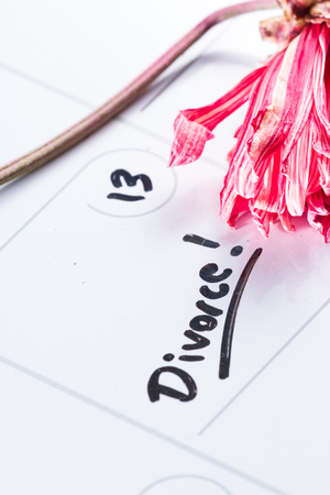 the word divorce hand written on a dry erase calendar with a dead flower next to it Stock Photo